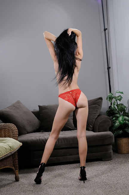 pretty, dark haired model topless in a red thong