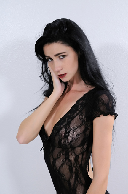 raven haired female standing in black lace lingerie