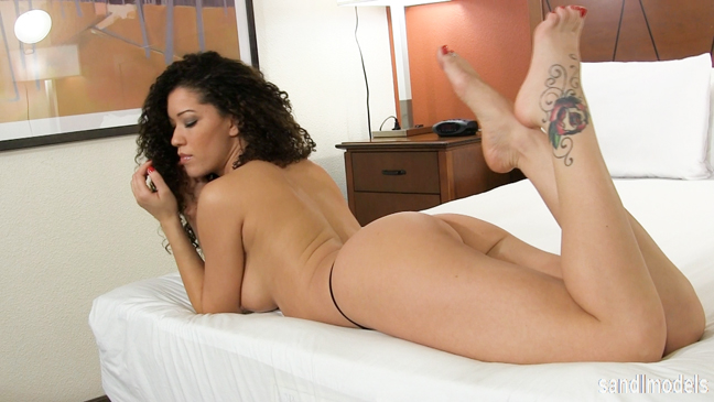 pretty female model with big hair lying topless on the bed