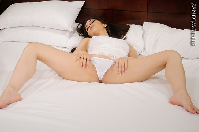 brunette female wearing a whie thong spreading on the bed
