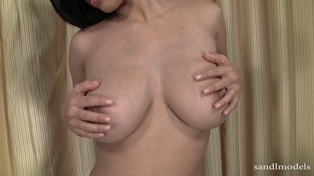 brunette female with her hands on her large breasts