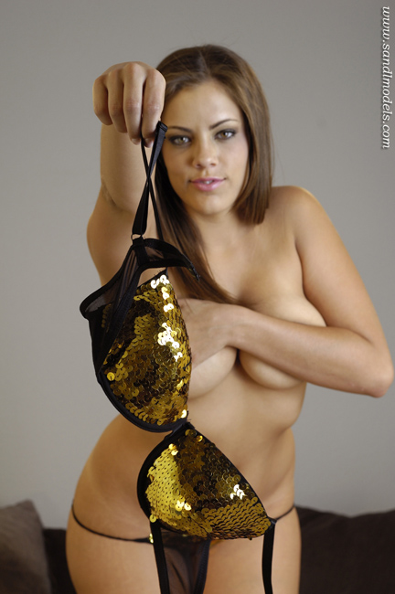 pretty latina model topless holding her bra in her hand